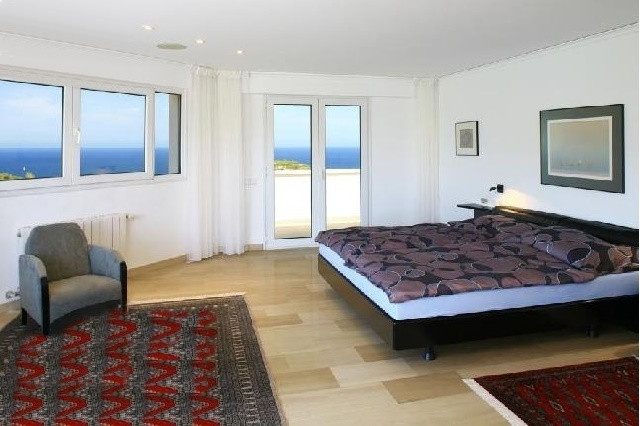 One of the elegant bedrooms with access to the terrace and heavenly views to the sea